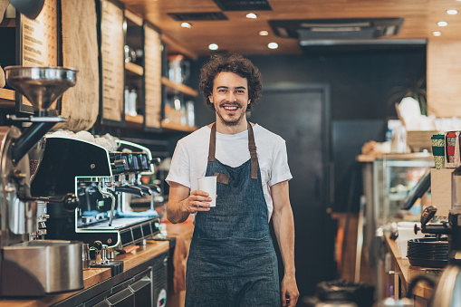 Smiling barista holding a coffee cup